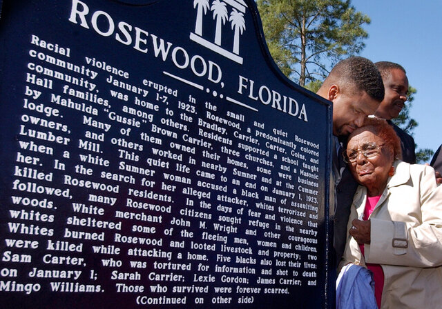 "FILE - In this Tuesday, May 4, 2004 file photo, living survivor of the 1923 violence in Rosewood, Fla., Robie Allenetta Mortin, is comforted by Florida Rep. Ed Jennings Jr. after he unveiled the Rosewood, Florida Historical marker at a dedication ceremony. On Jan. 1, 1923, a white woman in the neighboring community of Sumner alleged that she had been attacked in her home by an unidentified Black man, according to a 1993 report written by five scholars for the Florida Board of Regents. As the news of the woman's report spread to the white community, violence broke out. A Black church was burned, and then days later, a mob of at least 100 white people ""gathered and watched"" the burning of the remaining structures in the Black part of Rosewood. (Doug Finger/The Gainesville Sun via AP)"