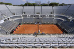 The stands around the Central Court of the Foro Italico are empty during a match between Serbia's Novak Djokovic and Italy's Salvatore Caruso, at the Italian Open tennis tournament in Rome, Wednesday, Sept. 16, 2020. The tournament at the Foro Italico was rescheduled from May because of the pandemic and is being played without fans in attendance. (Alfredo Falcone/LaPresse via AP)