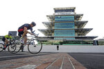 "IndyCar driver Spencer Pigot rides his bicycle across the ""Yard of Bricks"" at Indianapolis Motor Speedway, Sunday, May 24, 2020, in Indianapolis. The Indianapolis 500 was postponed because of the coronavirus pandemic. The race will instead be held Aug. 23, three months later than its May 24 scheduled date. (AP Photo/Darron Cummings)"