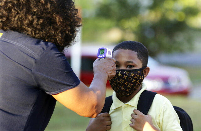 FILE - In this Monday, Aug. 24, 2020, file photo, fifth-grader Marcques Haley, 10, gets his temperature checked by school nurse Rachel White before entering Stephens Elementary School in Little Rock, Ark. The Little Rock teachers union said Sunday, Sept. 27, 2020, that its members won't show up for in-person classes due to concerns about the spread of coronavirus in schools. (Tommy Metthe/The Arkansas Democrat-Gazette via AP, File)