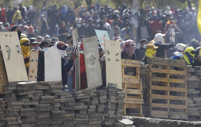 Anti-government demonstrators takes cover behind a barricade during clashes with police in Quito, Ecuador, Saturday, Oct. 12, 2019. Protests, which began when President Lenin Moreno's decision to cut subsidies led to a sharp increase in fuel prices, have persisted for days. (AP Photo/Fernando Vergara)
