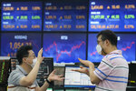 Currency traders gesture at the foreign exchange dealing room of the KEB Hana Bank headquarters in Seoul, South Korea, Friday, July 23, 2021. Asian markets were mixed on Friday after major indexes edged higher on Wall Street, preserving their gains for the week. (AP Photo/Ahn Young-joon)