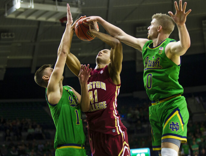 Boston College's Steffon Mitchell (41) tries to shoot past Notre Dame's Nate Laszewski (14) and Rex Pflueger (0) during an NCAA college basketball game Saturday, Dec. 7, 2019 at Purcell Pavilion in South Bend, Ind. (Michael Caterina/South Bend Tribune via AP)
