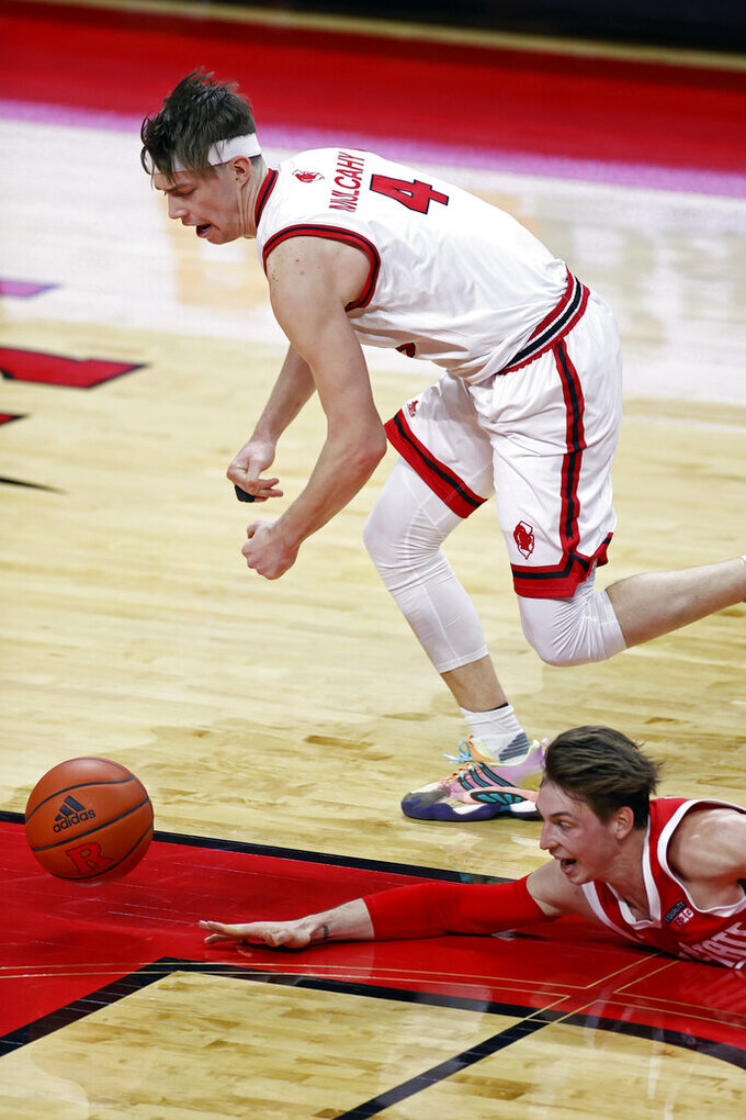 Ohio State guard Jimmy Sotos dives for a loose ball under Rutgers guard Paul Mulcahy (4) during the second half of an NCAA college basketball game Saturday, Jan. 9, 2021, in Piscataway, N.J. Ohio State won 79-68. Sotos was injured on the play. (AP Photo/Adam Hunger)