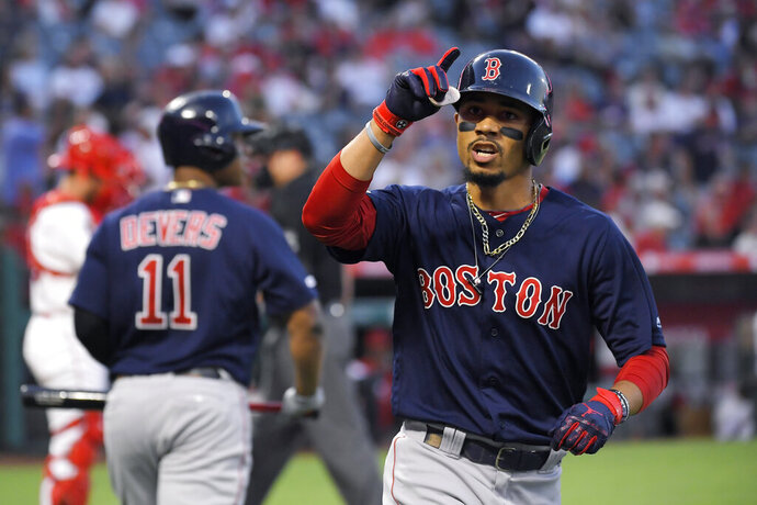 Boston Red Sox's Mookie Betts, right, gestures after scoring on a solo home run during the first inning of a baseball game against the Los Angeles Angels, Friday, Aug. 30, 2019, in Anaheim, Calif. (AP Photo/Mark J. Terrill)