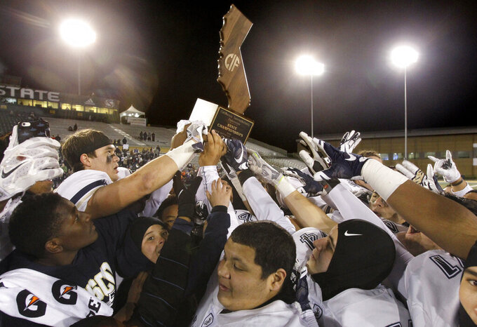 FILE - In this Saturday, Dec. 17, 2016 file photo, The St. John Bosco Braves celebrate their 56-33 defeat of De La Salle to win the Open Division high school football championship game in Sacramento, Calif. The California Interscholastic Federation, California's governing body for high school sports, said Monday, July 20, 2020 that the 2020-21 sports seasons will begin no earlier than December due to the coronavirus pandemic. The CIF said the normal fall, winter and spring sports seasons will be condensed into two seasons.(AP Photo/Steve Yeater, File)