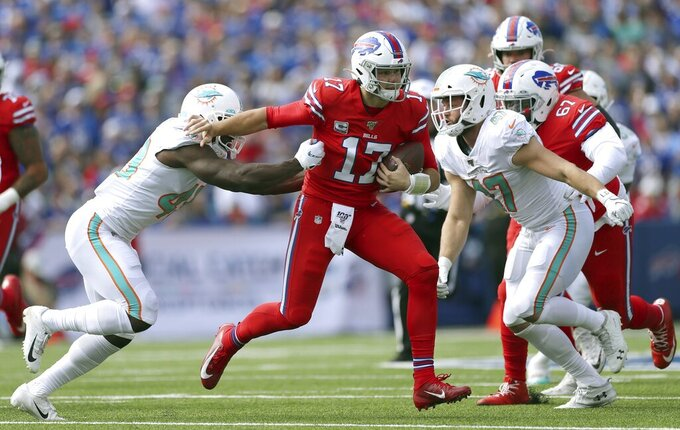 Buffalo Bills quarterback Josh Allen (17) tries to elude Miami Dolphins linebackers Sam Eguavoen, left, and Vince Biegel, right, in the first half of an NFL football game, Sunday, Oct. 20, 2019, in Orchard Park, N.Y. (AP Photo/Ron Schwane)