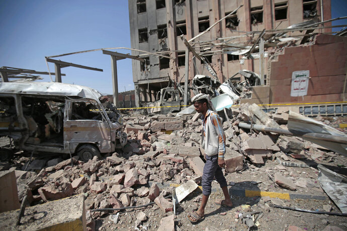 FILE - In this Feb. 4, 2018, file photo, a man inspects rubble after a Saudi-led coalition airstrike in Sanaa, Yemen. A leading Yemeni rebel figure said Thursday, Nov. 1, 2018, that the Trump administration's calls for a cease-fire in his country are
