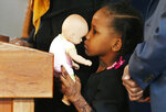 FILE - In this Feb. 3, 2017, file photo, four-year-old Somali refugee Mushkaad Abdi holds her doll as her mother, Samira Dahir, talks during a Minneapolis news conference one day after she was reunited with her family. Her trip from Uganda to Minnesota was held up by President Donald Trump's Jan. 27, 2017, order barring refugees from seven predominantly Muslim nations. Trump appears to be ignoring a deadline to establish how many refugees will be allowed into the United States in 2021, raising uncertainty about the future of the 40-year-old resettlement program that has been dwindling under the administration. (AP Photo/Jim Mone, File)