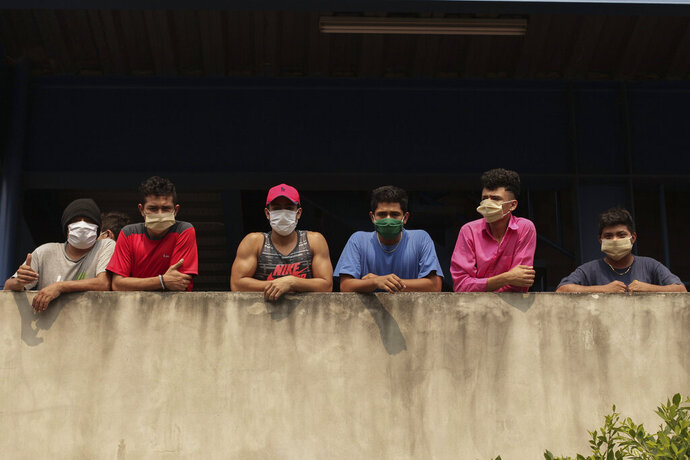 In this May 4, 2020 photo, men wearing protective face masks look out from a building where they are being held for violating a quarantine decreed by the government as part of measures to curb the spread of COVID-19, in San Salvador, El Salvador. The detained range from business executives returning from abroad to parents stopped by police while out to buy groceries.(AP Photo/Salvador Melendez)