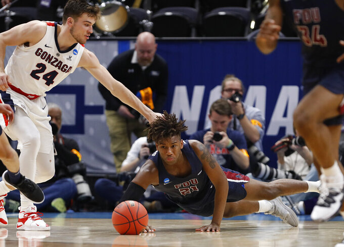 Fairleigh Dickinson forward Elyjah Williams dives for the ball next to Gonzaga forward Corey Kispert (24) during the second half of a first-round game in the NCAA men's college basketball tournament Thursday, March 21, 2019, in Salt Lake City. (AP Photo/Jeff Swinger)