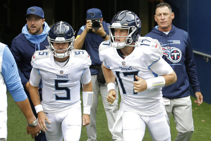 Tennessee Titans quarterback Ryan Tannehill (17) and backup quarterback Logan Woodside (5) take the field for warmups before an NFL football game against the Seattle Seahawks, Sunday, Sept. 19, 2021, in Seattle. (AP Photo/John Froschauer)