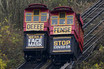 The cars on the Duquesne Incline pass each other carrying signs encouraging face mask wearing on Sunday, Nov. 22, 2020 in downtown Pittsburgh. (AP Photo/Gene J. Puskar)