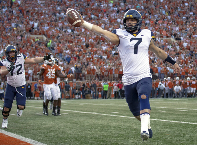 FILE - In this Nov. 3, 2018, file photo, West Virginia quarterback Will Grier (7) scores the game-winning two-point conversion during an NCAA college football game against Texas, in Austin, Texas.  Grier, a senior, will play in his final home game Friday night, Nov. 23, when No. 12 West Virginia hosts No. 6 Oklahoma. (Nick Wagner/Austin American-Statesman via AP, File)