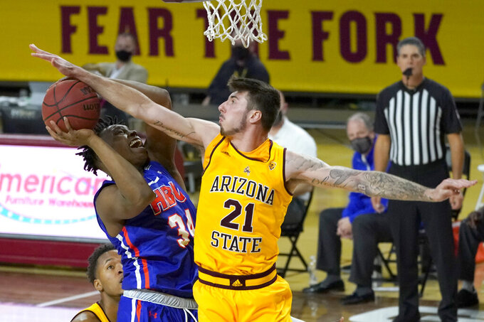 Arizona State forward Chris Osten (21) blocks the shot of Houston Baptist center Zach Iyeyemi during the second half of an NCAA college basketball game, Sunday, Nov. 29, 2020, in Tempe, Ariz. (AP Photo/Rick Scuteri)