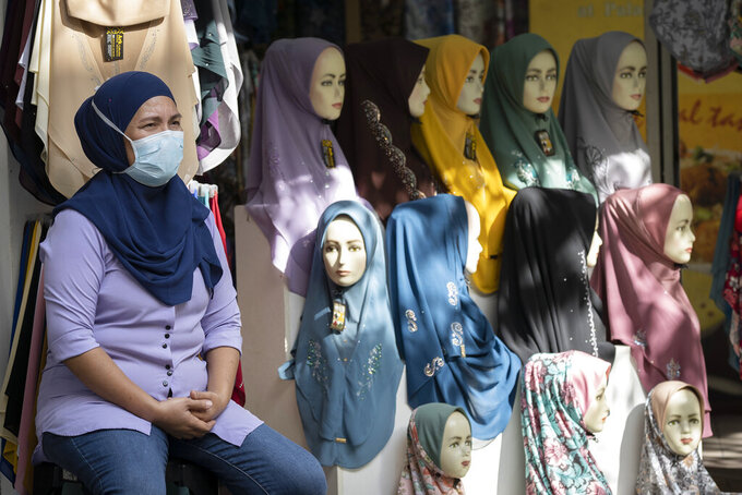 FILE - In this May 11, 2020, file photo, a shop vendor wearing a face mask to help curb the spread of the coronavirus waits for customers outside headscarves shop in Kuala Lumpur, Malaysia. Malaysia has reported its economy contracted 17% in the last quarter in its worst downturn since the global financial crisis. (AP Photo/Vincent Thian, File)