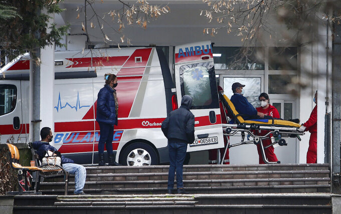 In this picture taken on Tuesday, Dec. 29, 2020, health workers wheel out a patient from an ambulance, at the entrance of the University Clinic complex in Skopje, North Macedonia. When thousands of people across the European Union simultaneously began rolling up their sleeves last month to get a coronavirus vaccination shot, one corner of the continent was left behind, feeling isolated and abandoned: the Balkans. (AP Photo/Boris Grdanoski)