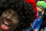 In this Saturday, Nov. 12, 2016 file photo, a Black Pete interacts with children during the arrival of Sinterklaas in Maassluis, Netherlands, Saturday, Nov. 12, 2016. Saturday, Nov. 12, 2016. A court in the Netherlands has convicted 34 people on Friday NOv. 9, 2018, who blocked a highway last year to prevent anti-racism demonstrators reaching the nationally televised arrival of Sinterklaas, the Dutch version of Santa Claus, and his helpers called