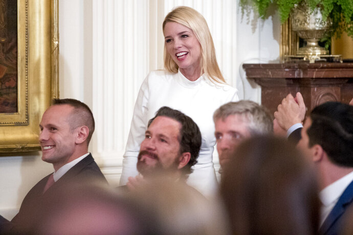 """In this April 1, 2019, photo, former Florida attorney general Pam Bondi is recognized by President Donald Trump at the 2019 Prison Reform Summit and First Step Act Celebration in the East Room of the White House in Washington. The White House is beefing up its communications staff as it tries to grapple with the ongoing House impeachment investigation. A senior administration official tells The Associated Press that Bondi, and Tony Sayegh, a former Treasury Department spokesman, are expected to join the White House communications team to work on """"proactive impeachment messaging"""" and other special projects. (AP Photo/Andrew Harnik, file)"""