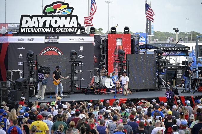 Entertainer Chris Lane, center, performs with a fan before a NASCAR Cup Series auto race at Daytona International Speedway, Saturday, Aug. 28, 2021, in Daytona Beach, Fla. (AP Photo/Phelan M. Ebenhack)