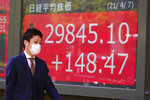 A man wearing a protective mask walks in front of an electronic stock board showing Japan's Nikkei 225 index at a securities firm Wednesday, April 7, 2021, in Tokyo. Asian shares were mixed Wednesday after Wall Street took a breather, with major indexes edging lower. (AP Photo/Eugene Hoshiko)