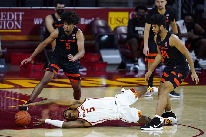 Southern California guard Isaiah White (5) reaches for the ball near Oregon State guard Ethan Thompson (5) and forward Isaiah Johnson (24) during the first half of an NCAA college basketball game Thursday, Jan. 28, 2021, in Los Angeles. (AP Photo/Ashley Landis)