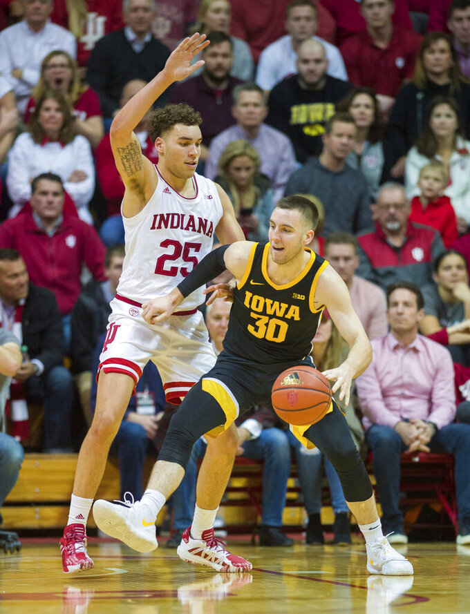 Indiana forward Race Thompson (25) defends against Iowa guard Connor McCaffery (30) who works the ball toward the basket during the first half of an NCAA college basketball game, Thursday, Feb. 13, 2020, in Bloomington, Ind. (AP Photo/Doug McSchooler)