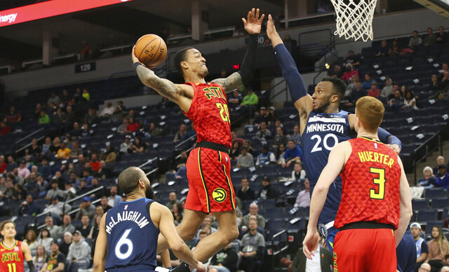 Atlanta Hawks' John Collins, center left, goes up for a shot as Minnesota Timberwolves' Josh Okogie of Nigeria defends in the second half of an NBA basketball game Wednesday, Feb. 5, 2020, in Minneapolis. The Hawks won 127-120. Collins scored 27 points and had 12 rebounds. Okogie scored 23 points for the Timberwolves. (AP Photo/Jim Mone)