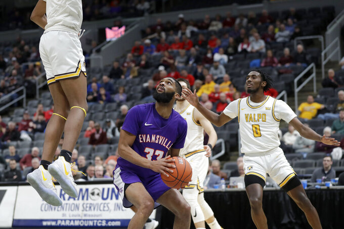 Evansville's K.J. Riley (33) looks to the basket as Valparaiso's Donovan Clay, left, and Javon Freeman-Liberty (0) defend during the first half of an NCAA college basketball game in the first round of the Missouri Valley Conference men's tournament Thursday, March 5, 2020, in St. Louis. (AP Photo/Jeff Roberson)