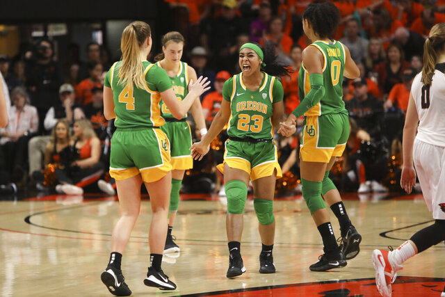 Oregon's Minyon Moore (23) celebrates with Jaz Shelley (4), Sabrina Ionescu (20) and Satou Sabally (0) following Oregon's victory over Oregon State in an NCAA college basketball game in Corvallis, Ore., Sunday, Jan. 26, 2020. (AP Photo/Amanda Loman)