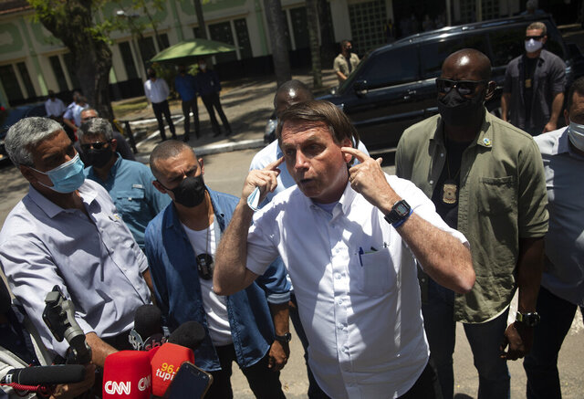 Brazil's President Jair Bolsonaro talks with the media outside a polling station, after voting during the run-off municipal elections in Rio de Janeiro, Brazil, Sunday, Nov. 29, 2020. Bolsonaro, who sometimes has embraced the label