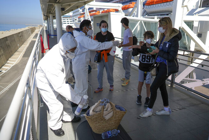 Passengers, from right, Stefania Battistoni, her sons Dasteen and Samuel Pacifici and her mother Loredana Merlo have their hand luggage sanitized prior to boarding the MSC Grandiosa cruise ship in Civitavecchia, near Rome, Wednesday, March 31, 2021. MSC Grandiosa, the world's only cruise ship to be operating at the moment, left from Genoa on March 30 and stopped in Civitavecchia near Rome to pick up more passengers and then sail toward Naples, Cagliari, and Malta to be back in Genoa on April 6. For most of the winter, the MSC Grandiosa has been a lonely flag-bearer of the global cruise industry stalled by the pandemic, plying the Mediterranean Sea with seven-night cruises along Italy's western coast, its major islands and a stop in Malta. (AP Photo/Andrew Medichini)