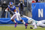 New York Giants running back Saquon Barkley (26) runs with the ball as Miami Dolphins defensive back Nik Needham (40) holds on in the second half of an NFL football game, Sunday, Dec. 15, 2019, in East Rutherford, N.J. (AP Photo/Adam Hunger)