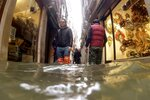 People make their way through water in Venice, Italy, Friday, Nov. 15, 2019. Exceptionally high tidal waters returned to Venice on Friday, prompting the mayor to close the iconic St. Mark's Square and call for donations to repair the Italian lagoon city just three days after it experienced its worst flooding in 50 years. (AP Photo/Luca Bruno)