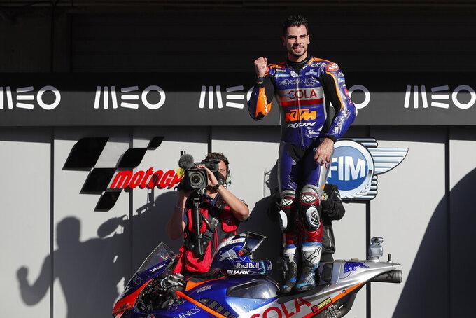 MotoGP rider Miguel Oliveira of Portugal celebrates after winning the MotoGP race of the Portuguese Motorcycle Grand Prix, the last race of the season, at the Algarve International circuit near Portimao, Portugal, Sunday, Nov. 22, 2020. (AP Photo/Armando Franca)