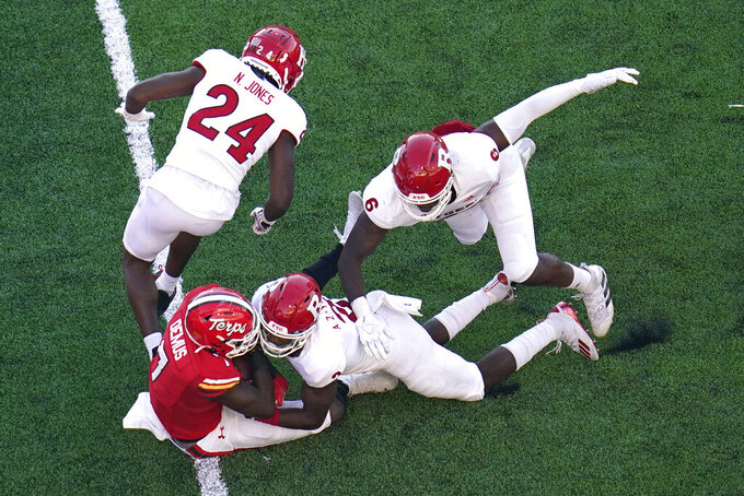 Maryland wide receiver Dontay Demus Jr. (7) falls into the end zone while scoring a touchdown as Rutgers defensive back Naijee Jones (24), defensive back Avery Young (2) and linebacker Rashawn Battle (6) try to stop him during the second half of an NCAA college football game, Saturday, Dec. 12, 2020, in College Park, Md. Rutgers won 27-24 in overtime. (AP Photo/Julio Cortez)