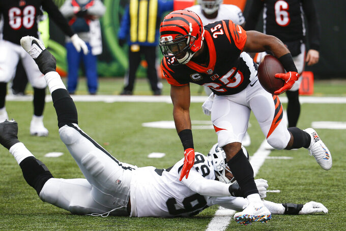 FILE - In this Dec. 16, 2018, file photo, Cincinnati Bengals running back Giovani Bernard (25) breaks a tackle from Oakland Raiders defensive end Arden Key (99) in the first half of an NFL football game in Cincinnati. The Bengals signed Bernard to a two-year contract extension Tuesday, Sept. 3, 2019, through the 2021 season. He could have become a free agent after this season. (AP Photo/Frank Victores, File)