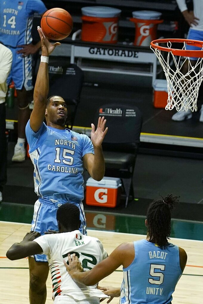 North Carolina forward Garrison Brooks (15) targets the basket over Miami forward Deng Gak (22) during the second half of an NCAA college basketball game, Tuesday, Jan. 5, 2021, in Coral Gables, Fla. (AP Photo/Marta Lavandier)