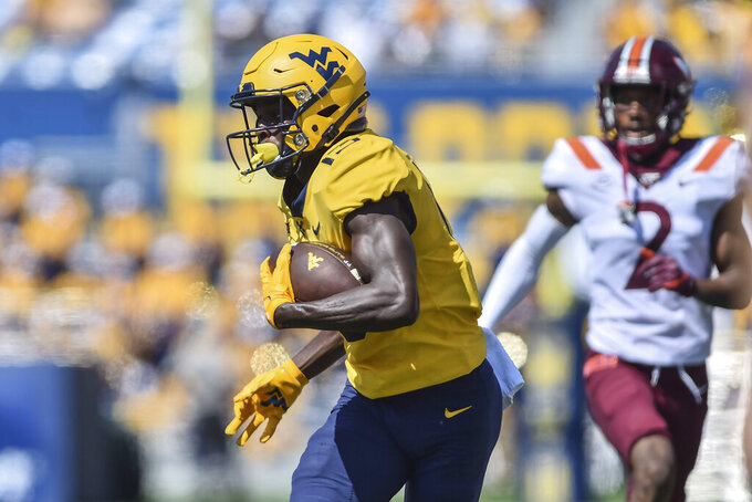 West Virginia wide receiver Sam James (13) picks up yardage after a catch against Virginia Tech during the first half of an NCAA college football game in Morgantown, W.Va., Saturday, Sept. 18, 2021. (AP Photo/William Wotring)