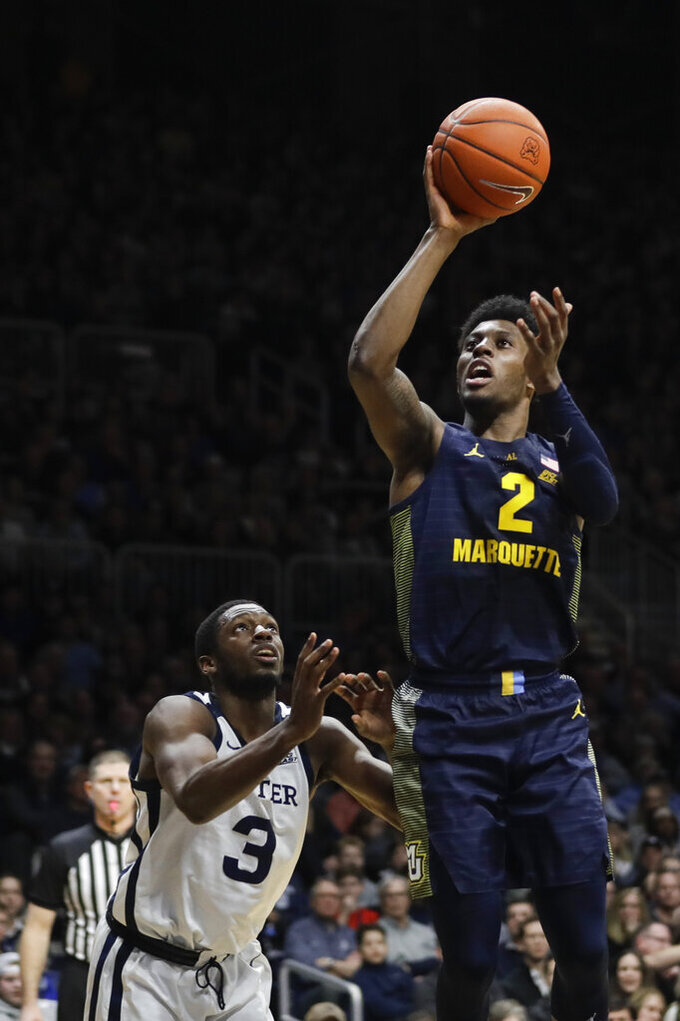 Marquette's Sacar Anim (2) shoots against Butler's Kamar Baldwin (3) during the second half of an NCAA college basketball game, Friday, Jan. 24, 2020, in Indianapolis. Butler won, 89-85, in overtime. (AP Photo/Darron Cummings)