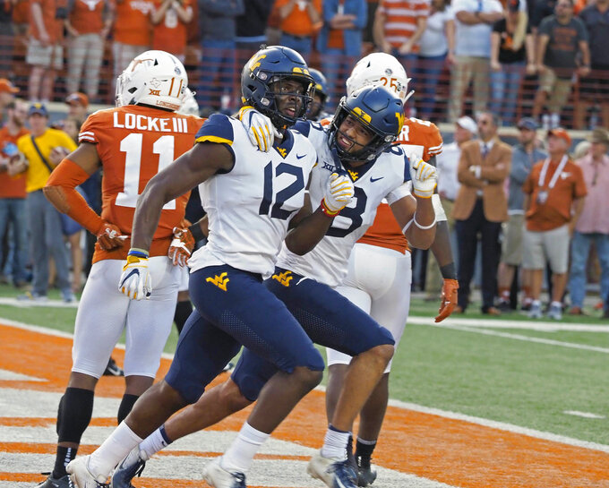 West Virginia receiver Gary Jennings (12) and Marcus Simms (8) celebrate Jenning's touchdown catch during the second half of an NCAA college football game against Texas, Saturday, Nov. 3, 2018, in Austin, Texas. West Virginia won 42-41. (AP Photo/Michael Thomas)