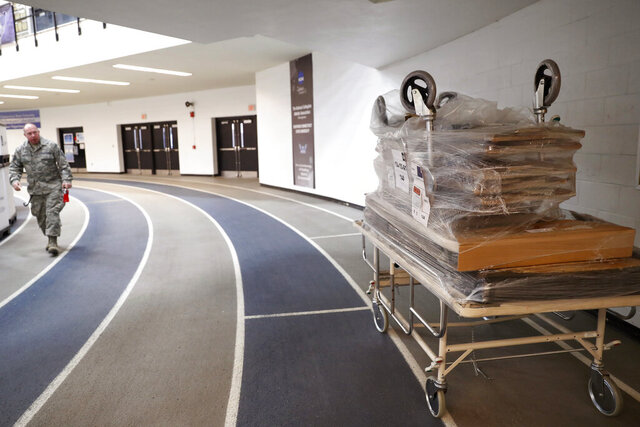 Hospital gurneys are stacked up, right, on an indoor track at Southern Connecticut State University's Moore Field House Tuesday, March 31, 2020, in New Haven, Conn., after Connecticut Air and Army National National Guard personnel unloaded supplies provided to the state by FEMA for a temporary field hospital to be constructed by week's end. The 250-bed capacity hospital will facilitate overflow in the event that regional hospitals treating COVID-19 patients reach their capacity. (AP Photo/Kathy Willens)