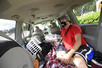 Jeff Lello sits in the van out of which he has been living, in the parking lot of a Cracker Barrel restaurant, since being laid off due to the coronavirus pandemic, Friday, Aug. 21, 2020, in Orlando, Fla. Lello is one of an estimated 20 million Americans living paycheck to paycheck, spending more than 30% of their income on rent, who are likely to experience homelessness at some point, according to the National Coalition for the Homeless. (AP Photo/Phelan M. Ebenhack)