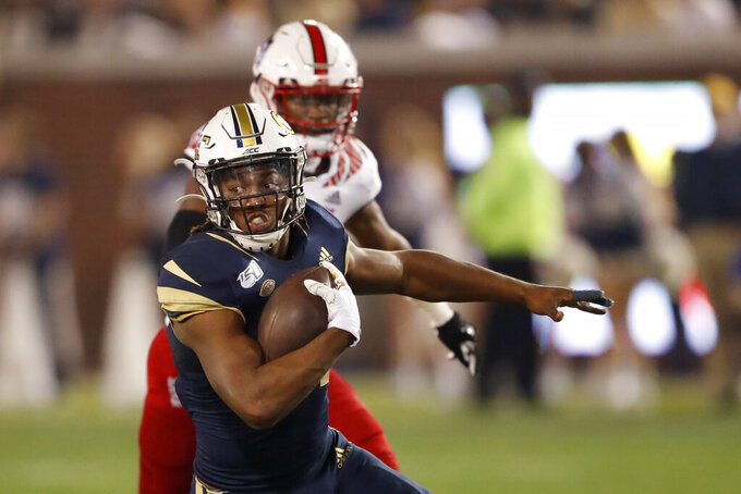 Georgia Tech running back Jordan Mason (27) looks for running room as he breaks through the North Carolina State defensive line during the first half of an NCAA college football game Thursday, Nov. 21, 2019, in Atlanta. (AP Photo/John Bazemore)