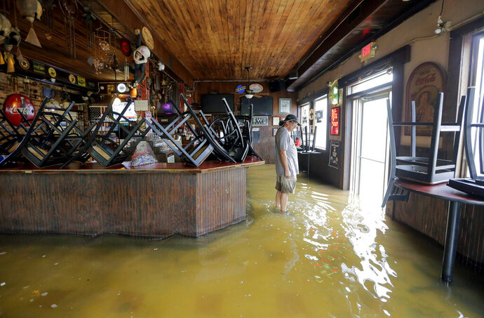 A man stands in floodwaters at Don'z On the Lake as Tropical Storm Barry's winds push water over the Lake Pontchartrain seawall Saturday, July 13, 2019. (David Grunfeld/The Advocate via AP)