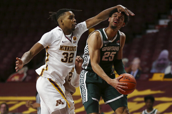 Michigan State's Malik Hall (25) is fouled by Minnesota's Sam Freeman (32) during the second half of an NCAA college basketball game, Monday, Dec. 28, 2020, in Minneapolis. Minnesota won 81-56. (AP Photo/Stacy Bengs)