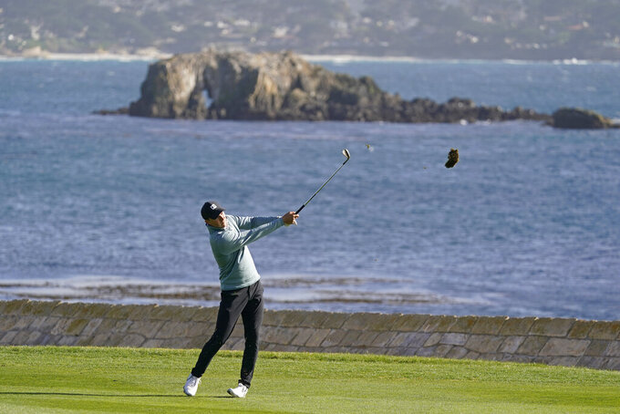 Jordan Spieth hits his approach shot to the 18th green of the Pebble Beach Golf Links during the third round of the AT&T Pebble Beach Pro-Am golf tournament Saturday, Feb. 13, 2021, in Pebble Beach, Calif. (AP Photo/Eric Risberg)