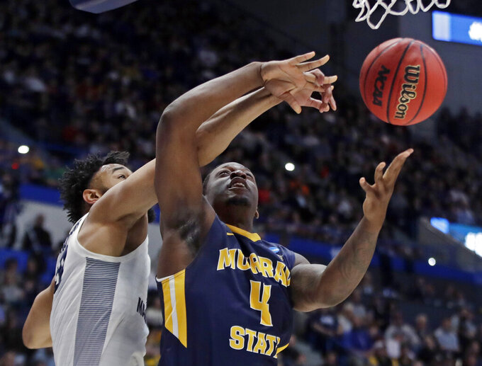 Marquette's Ed Morrow, left, blocks a shot by Murray State's Brion Sanchious (4) during the first half of a first round men's college basketball game in the NCAA Tournament, Thursday, March 21, 2019, in Hartford, Conn. (AP Photo/Elise Amendola)