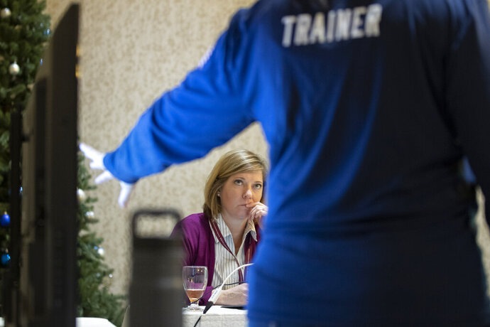 In this Monday, Dec. 16, 2019, photo, Karen Brenson Bell, from North Carolina, listens during an exercise run by military and national security officials, for state and local election officials to simulate different scenarios for the 2020 elections, in Springfield, Va. These government officials are on the front lines of a different kind of high-stakes battlefield, one in which they are helping to defend American democracy by ensuring free and fair elections. (AP Photo/Alex Brandon)