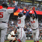 Atlanta Braves' Dansby Swanson, right, celebrates with Ronald Acuna Jr. (13) and Freddie Freeman (5) after hitting a three-run home run off San Francisco Giants' Jeff Samardzija during the second inning of a baseball game Wednesday, May 22, 2019, in San Francisco. (AP Photo/Ben Margot)